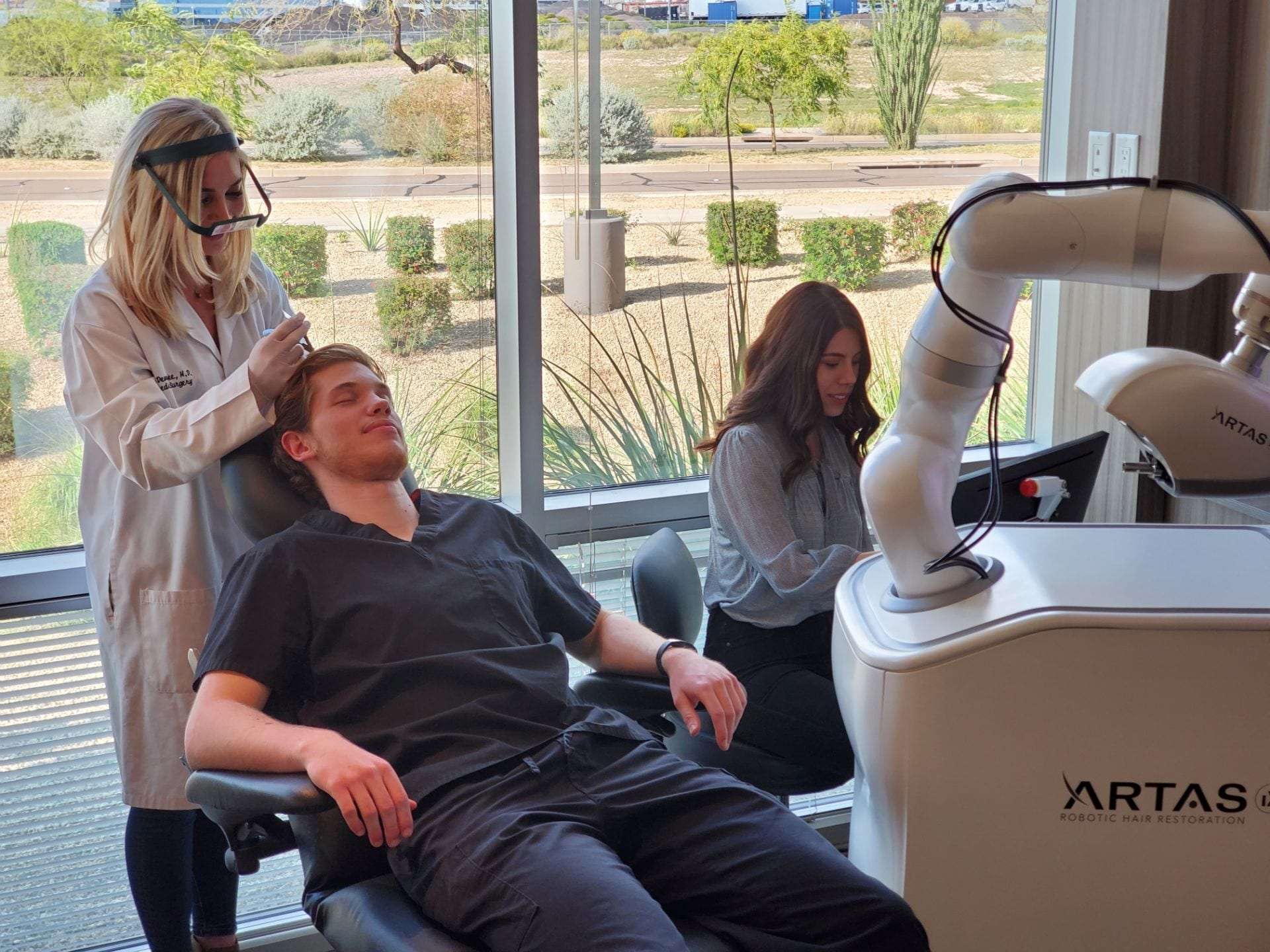 Robotic hair restoration procedure being done on a man.